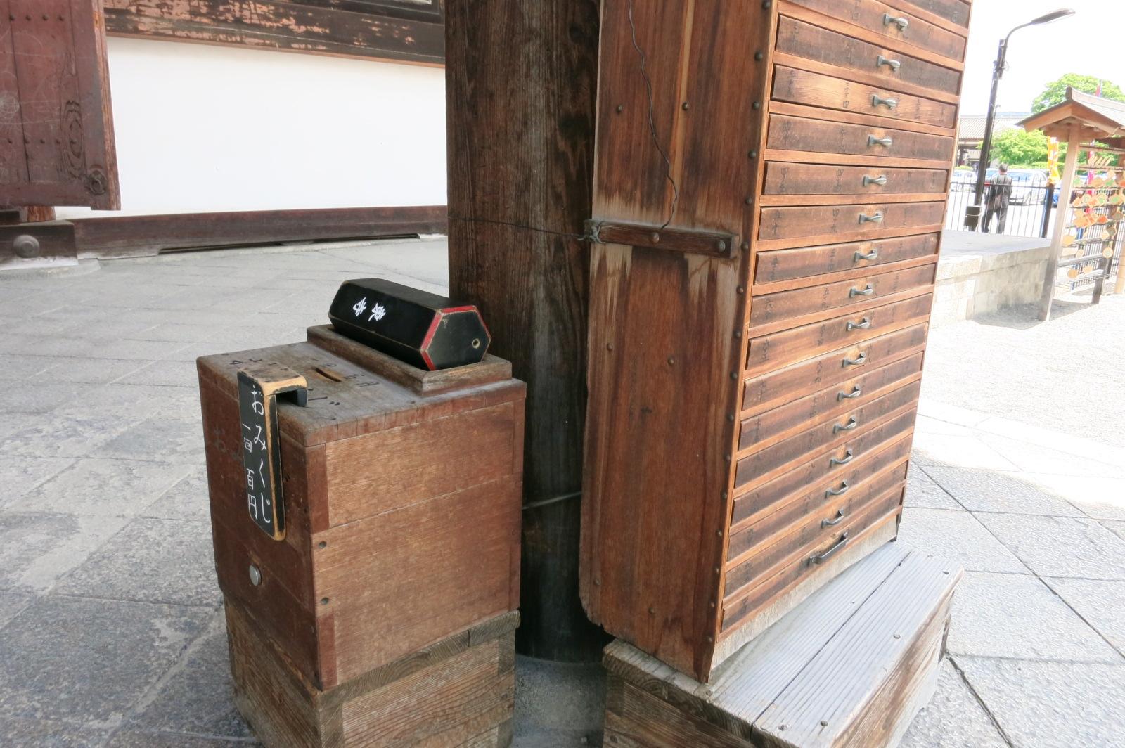 食堂(じきどう)前のおみくじ箱。黒い筒からくじ棒を出して、棒に書かれた数字の紙を棚から取り出します