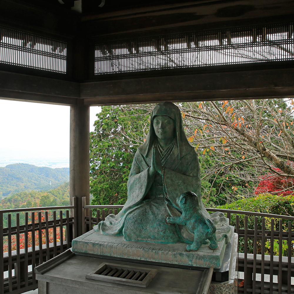 桂昌院の像。景色のいい高台に設置されています。椅子がありますので、休憩できます。