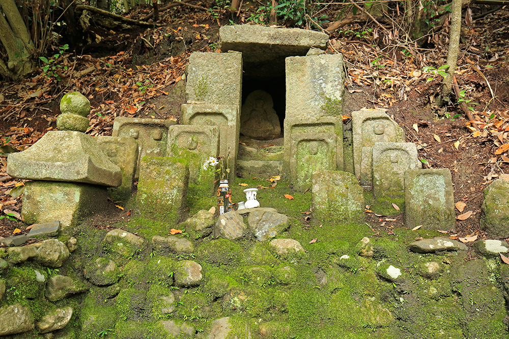 穴ヤクシ(薬師石仏)。板石の中に薬師如来石仏が祀られています。耳病に効のある仏様だそうです。