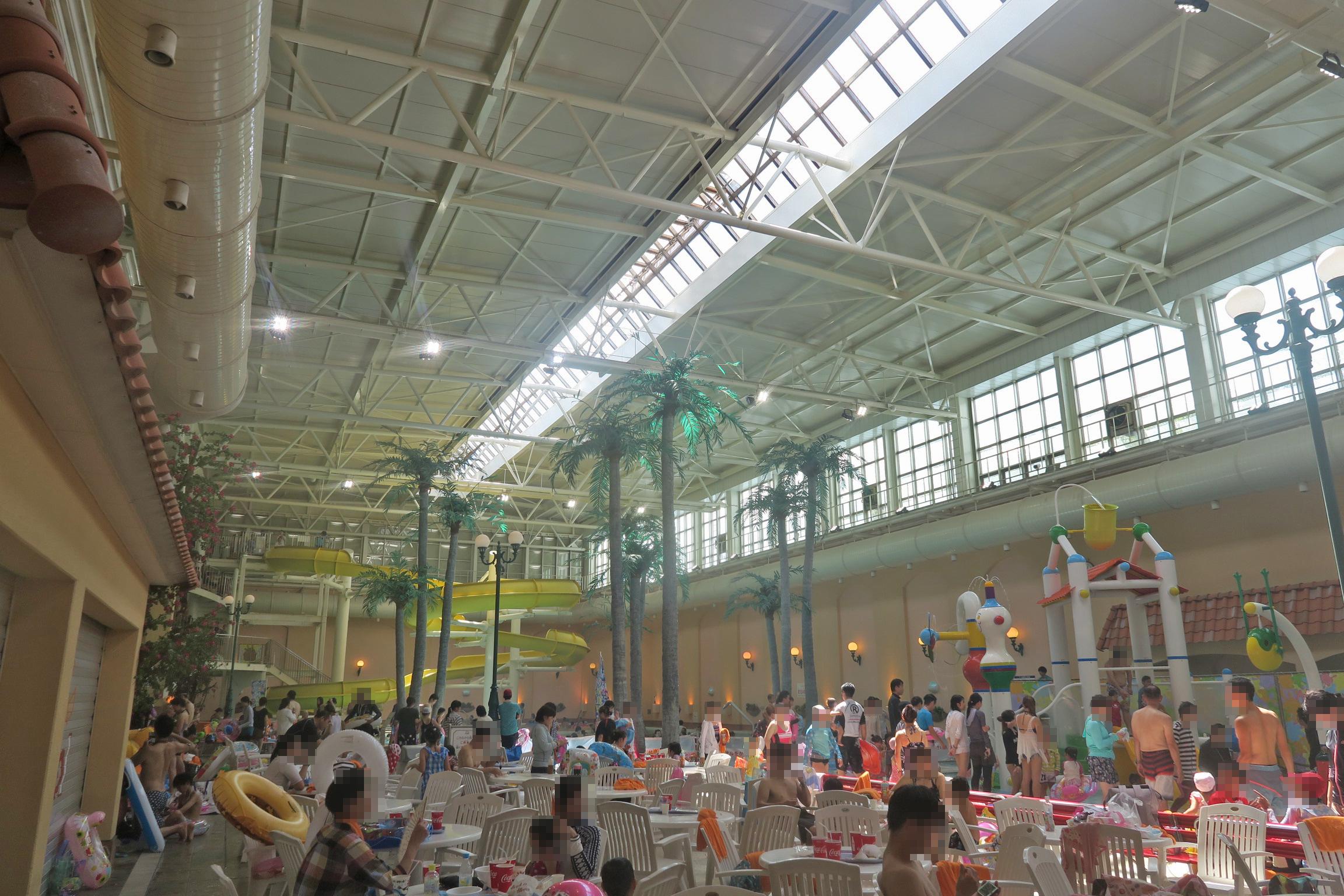 手前がテーブルとイスのある食事スペース。プールで遊んでいる人が席取りをしているので、空席がたくさん。
