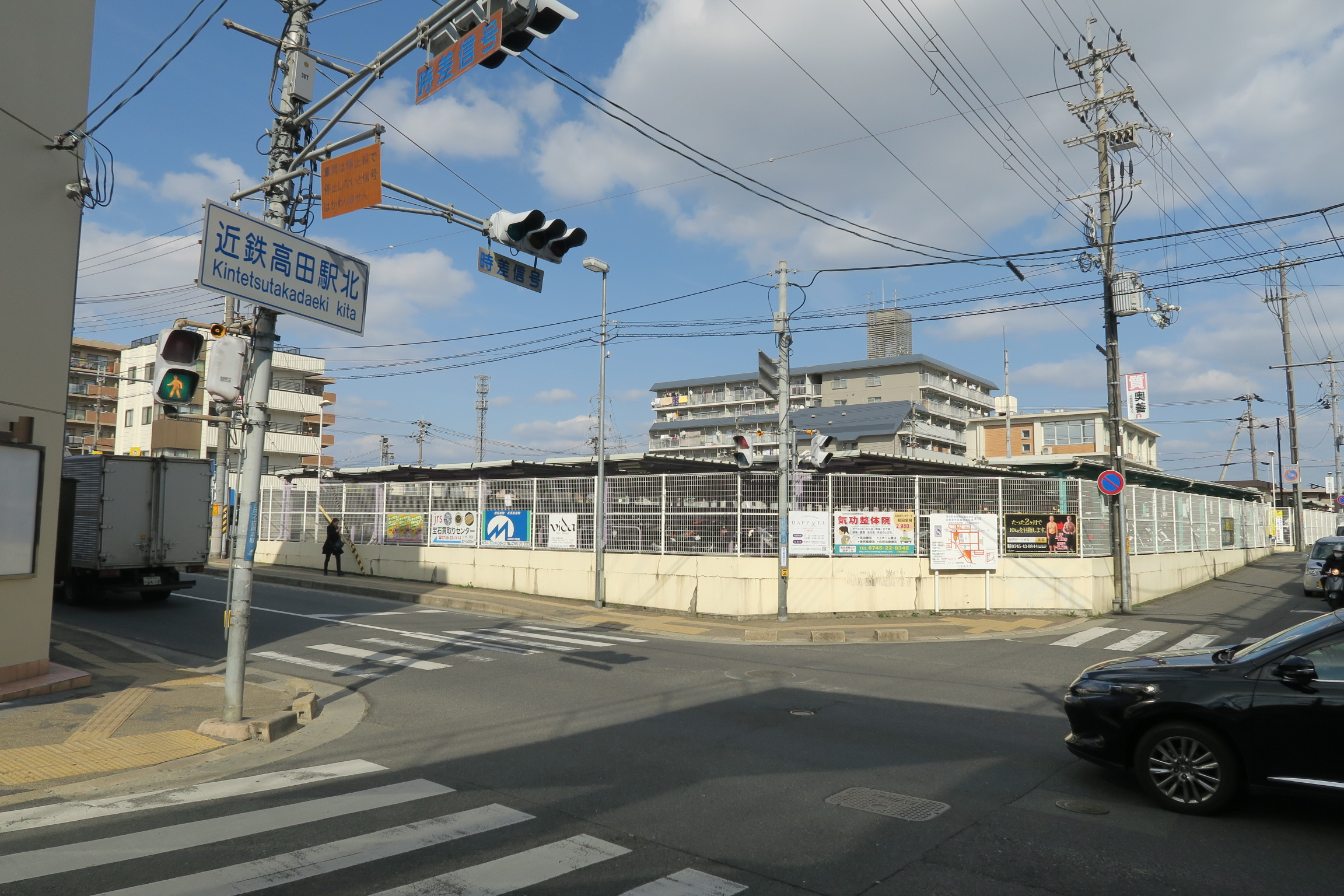 近鉄高田駅北の交差点。向かいは大きな駐輪場。左手方向に歩いていきます。